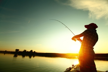 Young man fishing on a lake from the boat at sunset